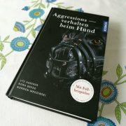 """Das Buch """"Aggression beim Hund"""" von Ute Heberer, Nora Brede und Normen Mrozinski Man sieht einen Hund mit Maulkorb"""